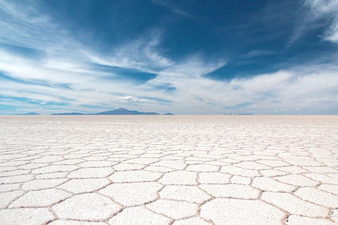 Cracked salt flats under a blue sky.